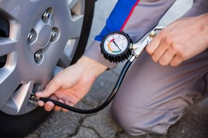 Person Measuring Car Tyre Pressure